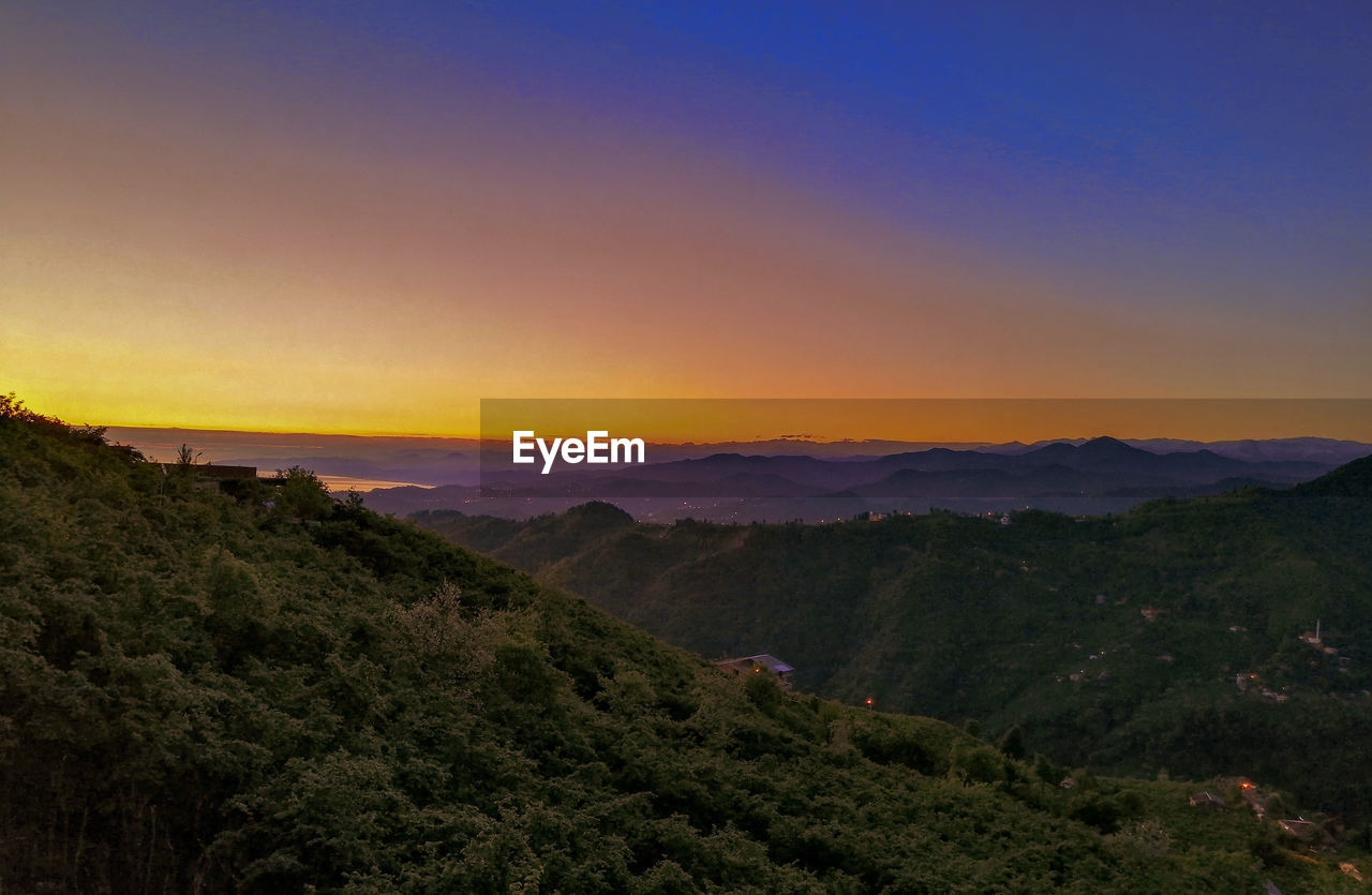HIGH ANGLE VIEW OF MOUNTAINS AGAINST SKY DURING SUNSET