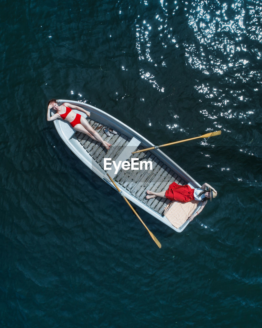 Directly Above View Of Women Lying In Boat On Lake