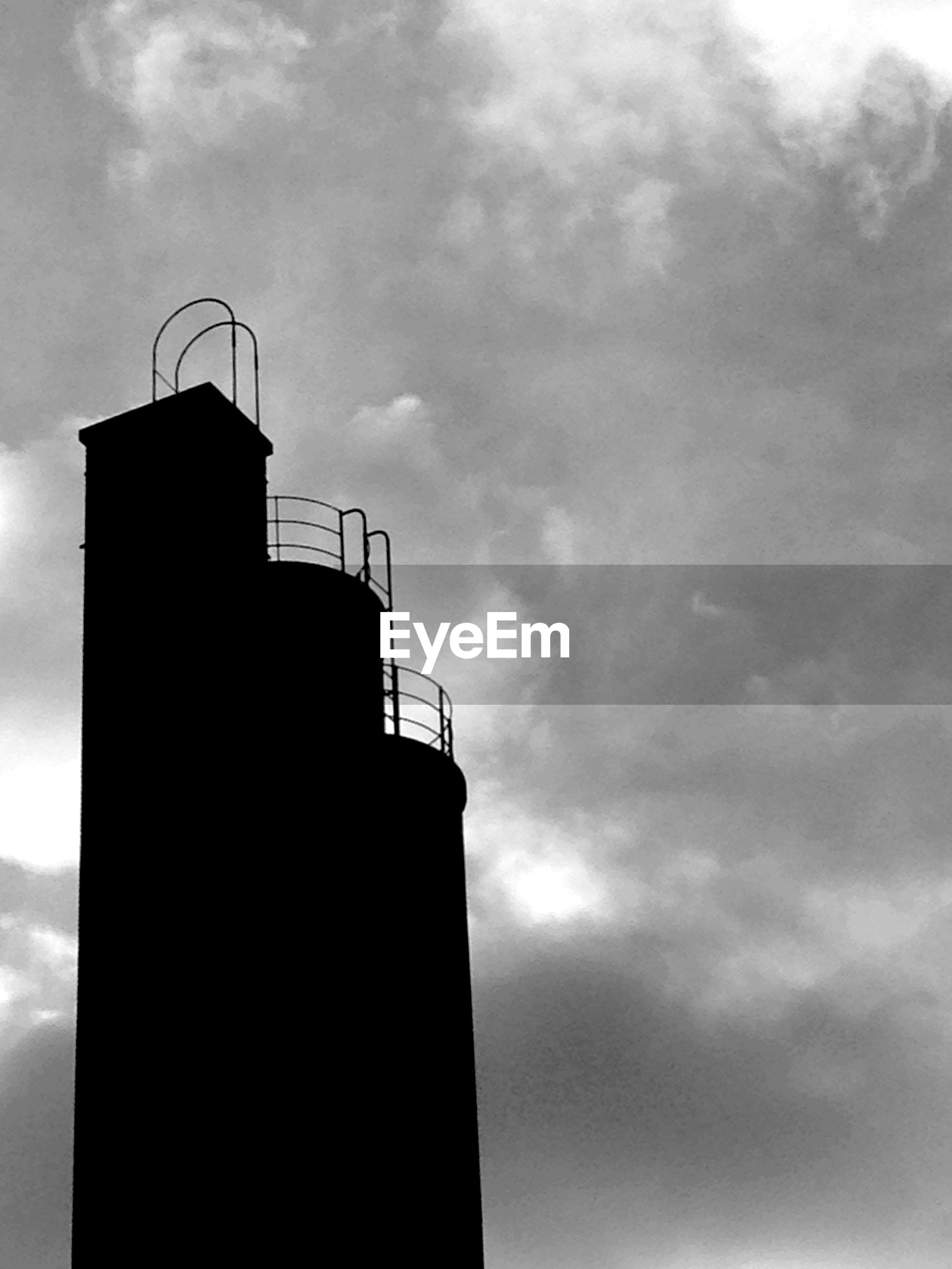 Low angle view of silhouette smoke stack against cloudy sky