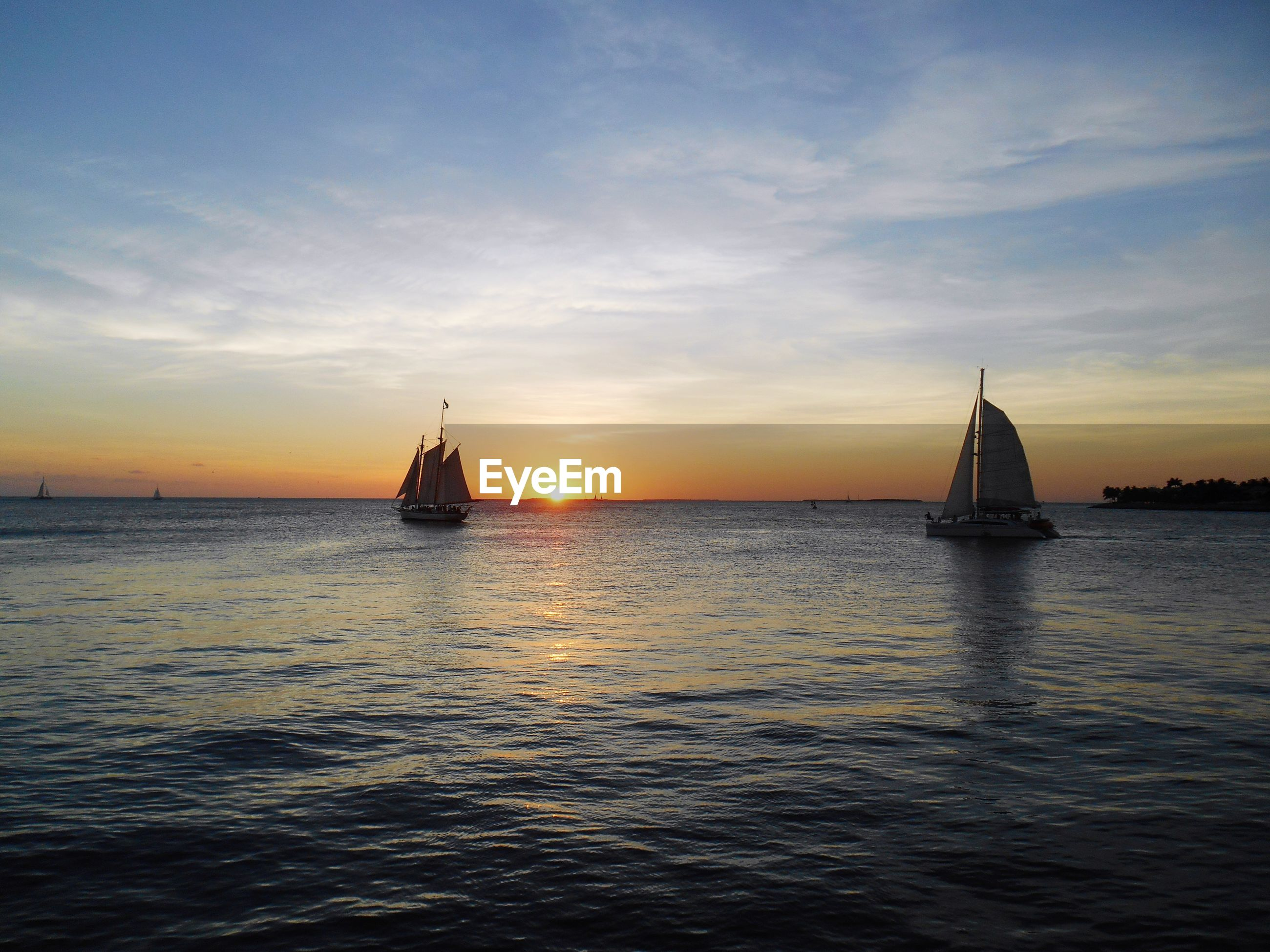 SAILBOATS SAILING ON SEA AGAINST SKY DURING SUNSET