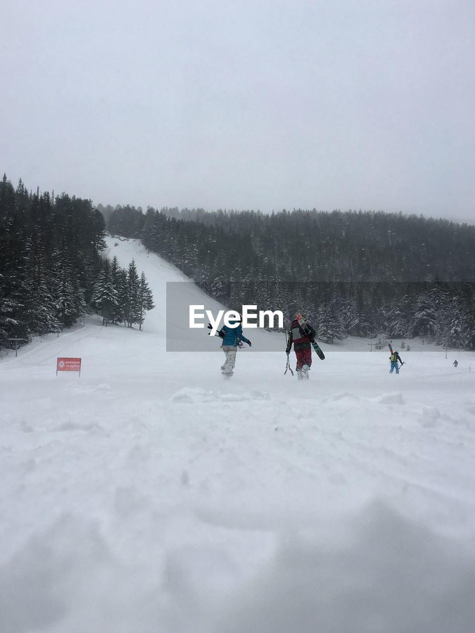People Walking On Snowy Field Against Sky