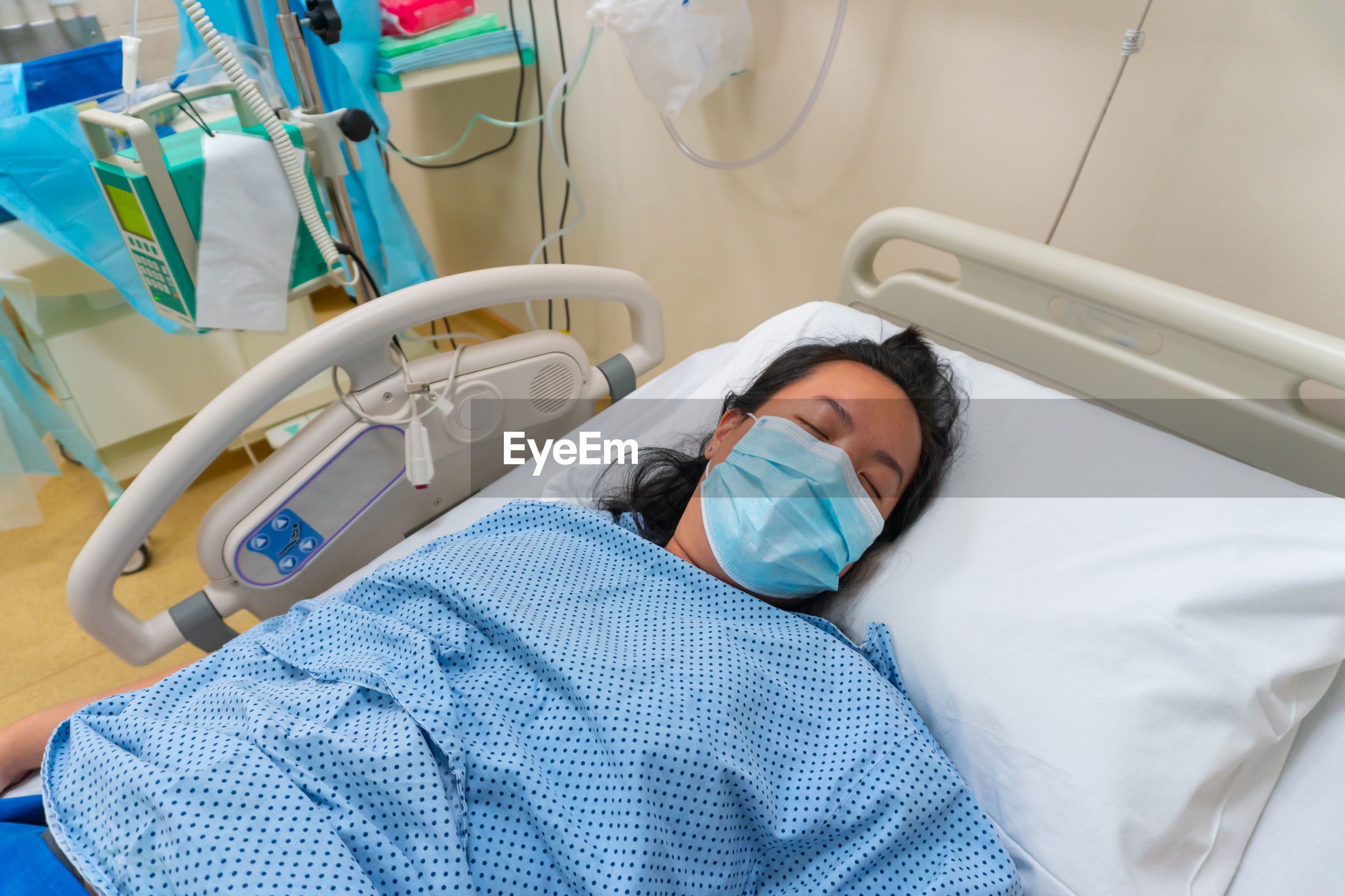 High angle view of woman lying on bed in hospital