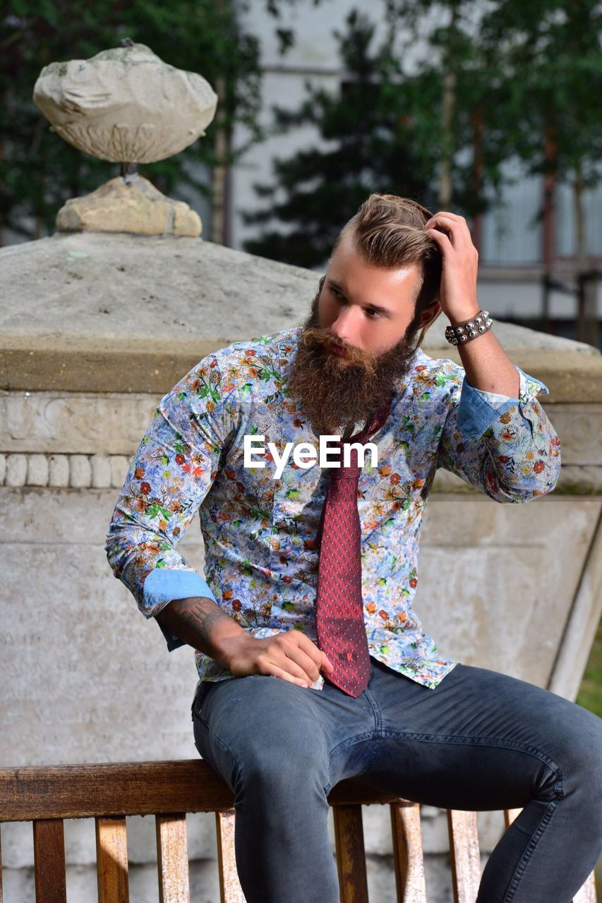 Hipster Looking Away While Sitting On Bench At Park