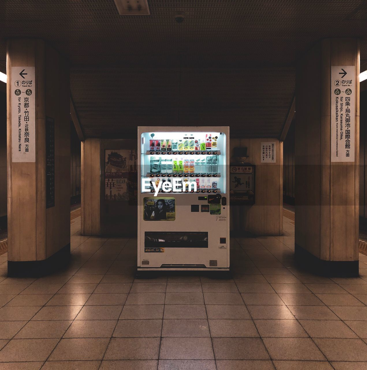 indoors, flooring, architecture, no people, communication, tile, built structure, text, illuminated, tiled floor, direction, empty, technology, western script, vending machine, appliance, wood - material, machinery, entrance, refrigerator, ceiling