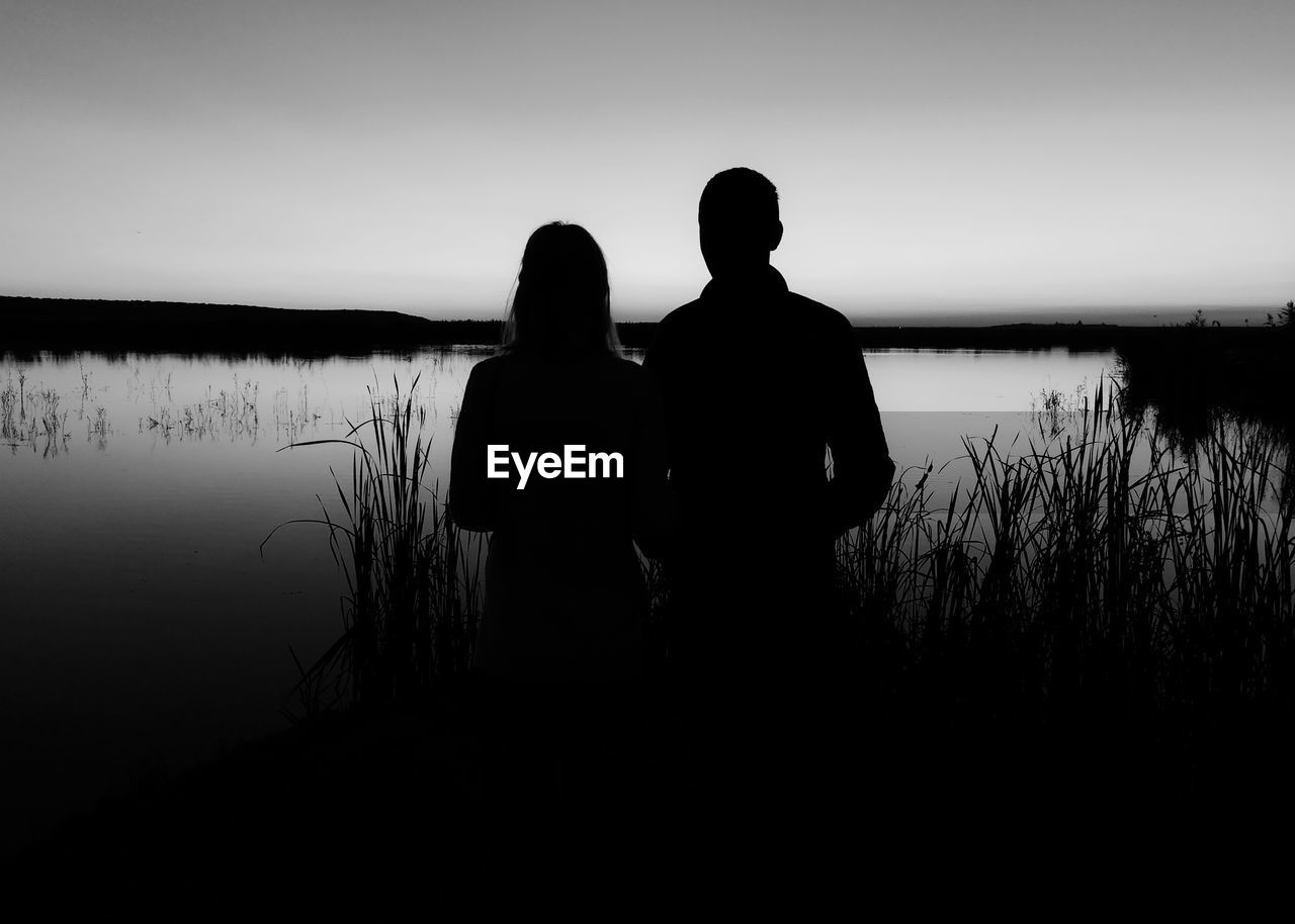 water, two people, lake, silhouette, real people, sky, standing, men, leisure activity, bonding, lifestyles, togetherness, tranquility, people, nature, rear view, couple - relationship, scenics - nature, love, positive emotion, outdoors