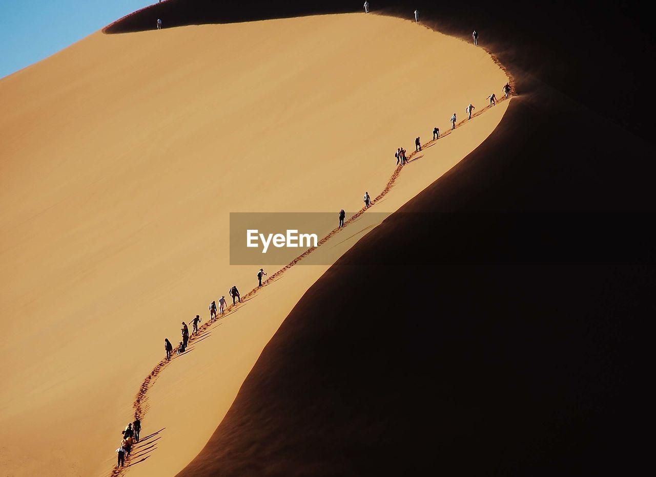 People walking on sand dune