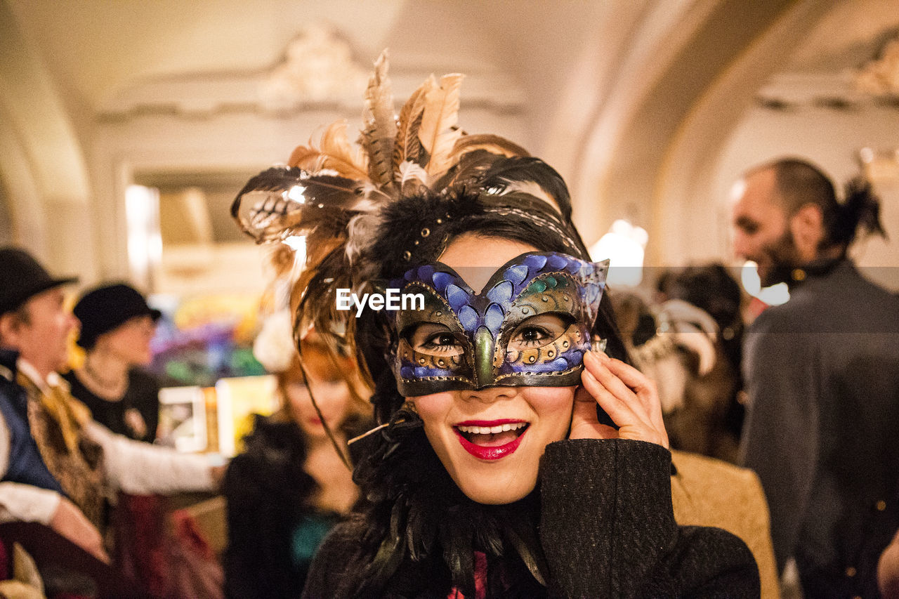 Portrait Of Happy Woman Wearing Masquerade Mask At Party