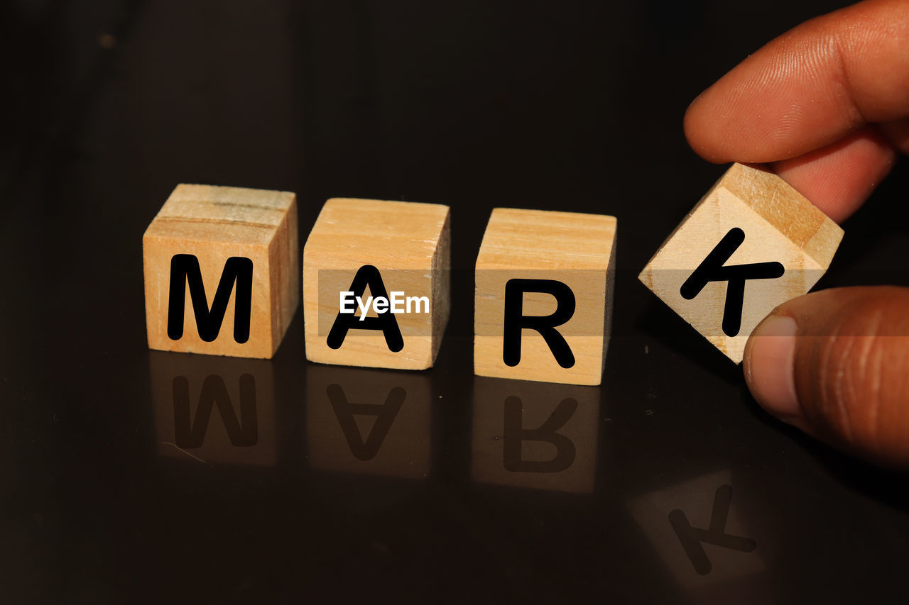Cropped hand with mark text on toy blocks against black background