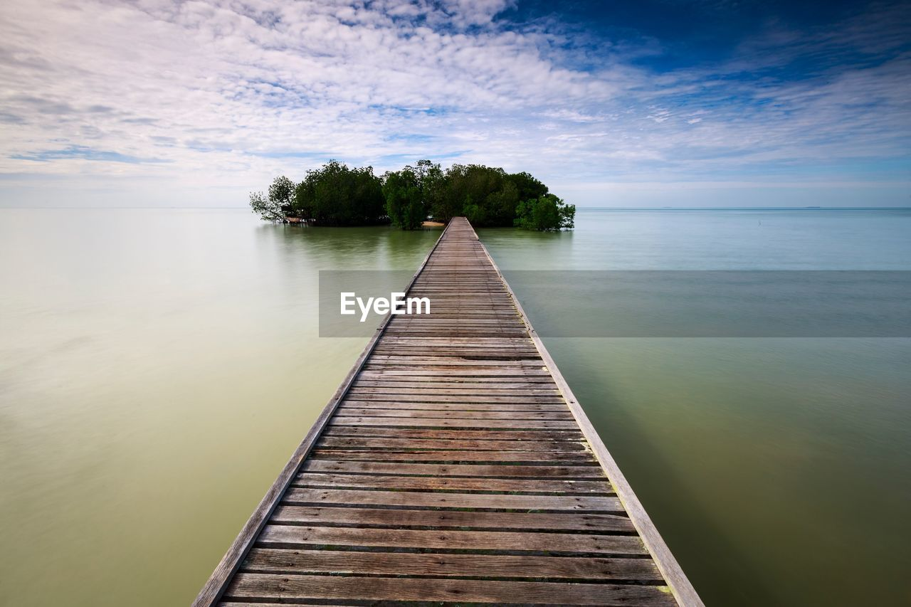 water, tranquil scene, beauty in nature, nature, sky, scenics, tranquility, pier, wood - material, no people, outdoors, lake, jetty, day, the way forward, wood paneling, tree, horizon over water