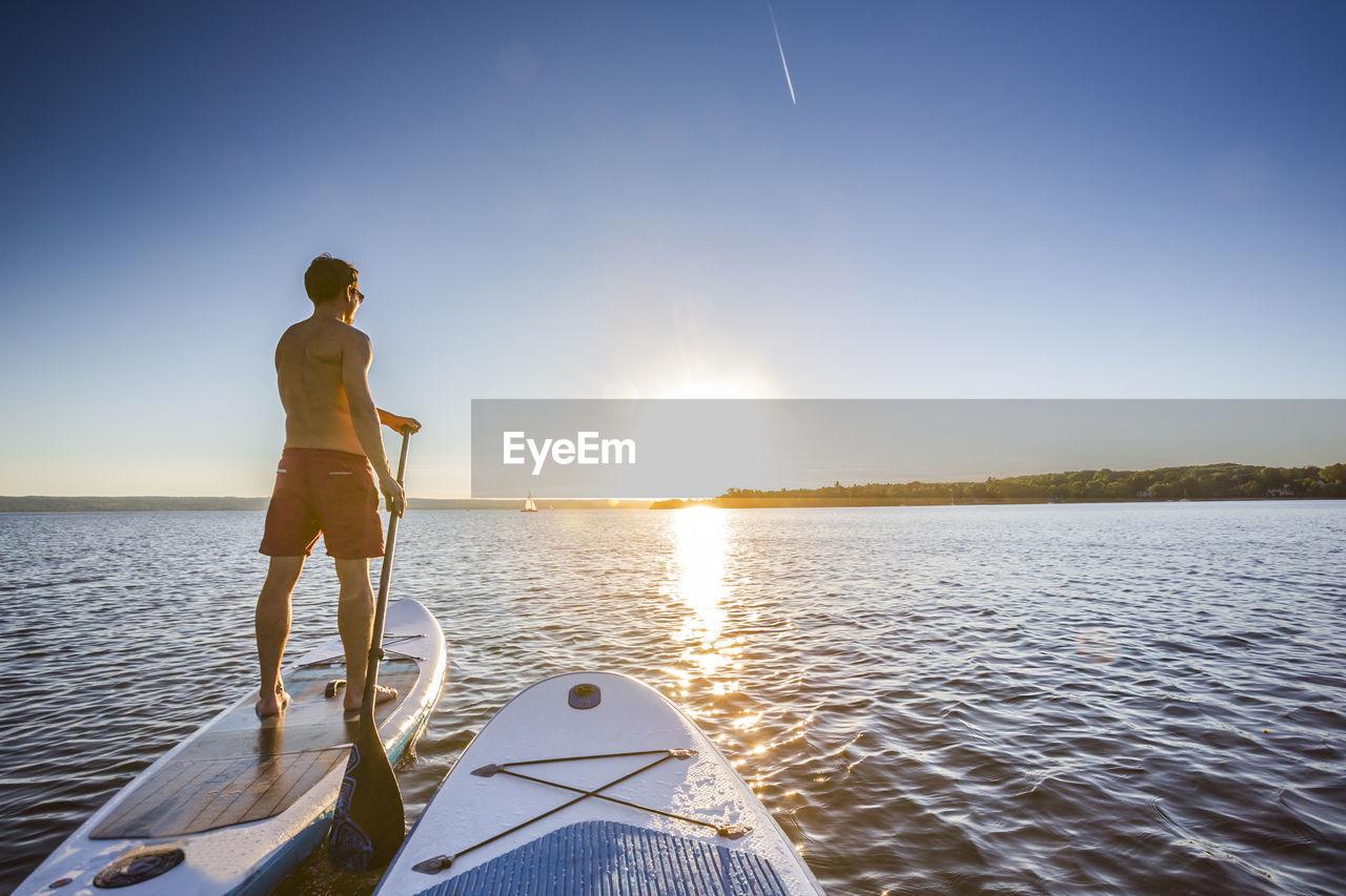Man Paddleboarding During Sunset