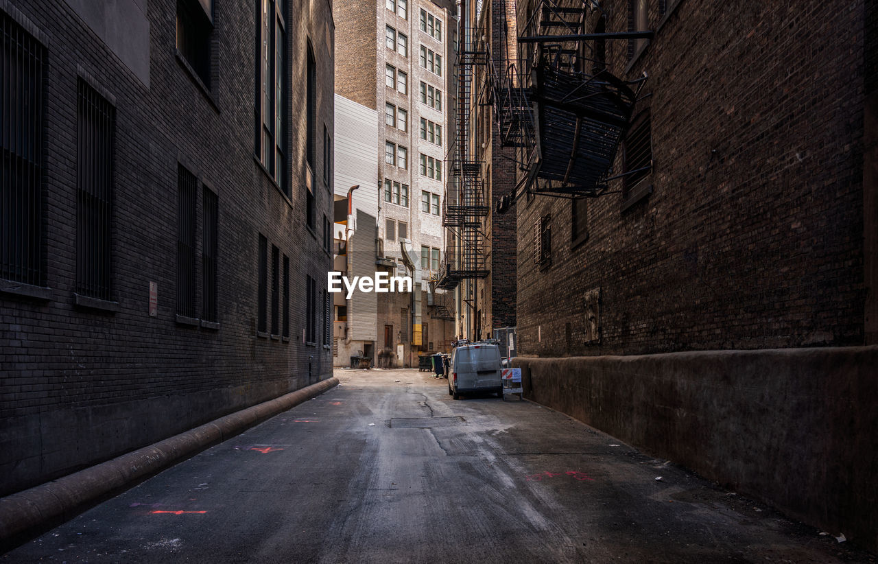 architecture, building exterior, motor vehicle, built structure, city, mode of transportation, transportation, car, land vehicle, street, building, road, direction, the way forward, no people, day, residential district, outdoors, city street, diminishing perspective, alley