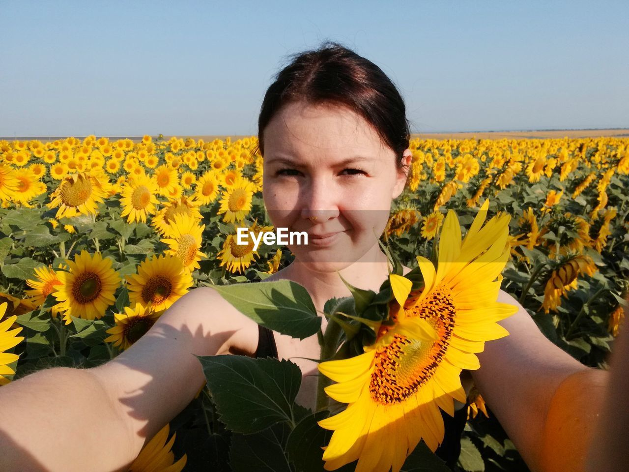 Portrait Of Woman Smiling While Standing At Sunflower Farm