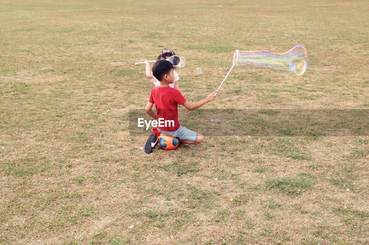 High angle view of children playing with bubbles on field