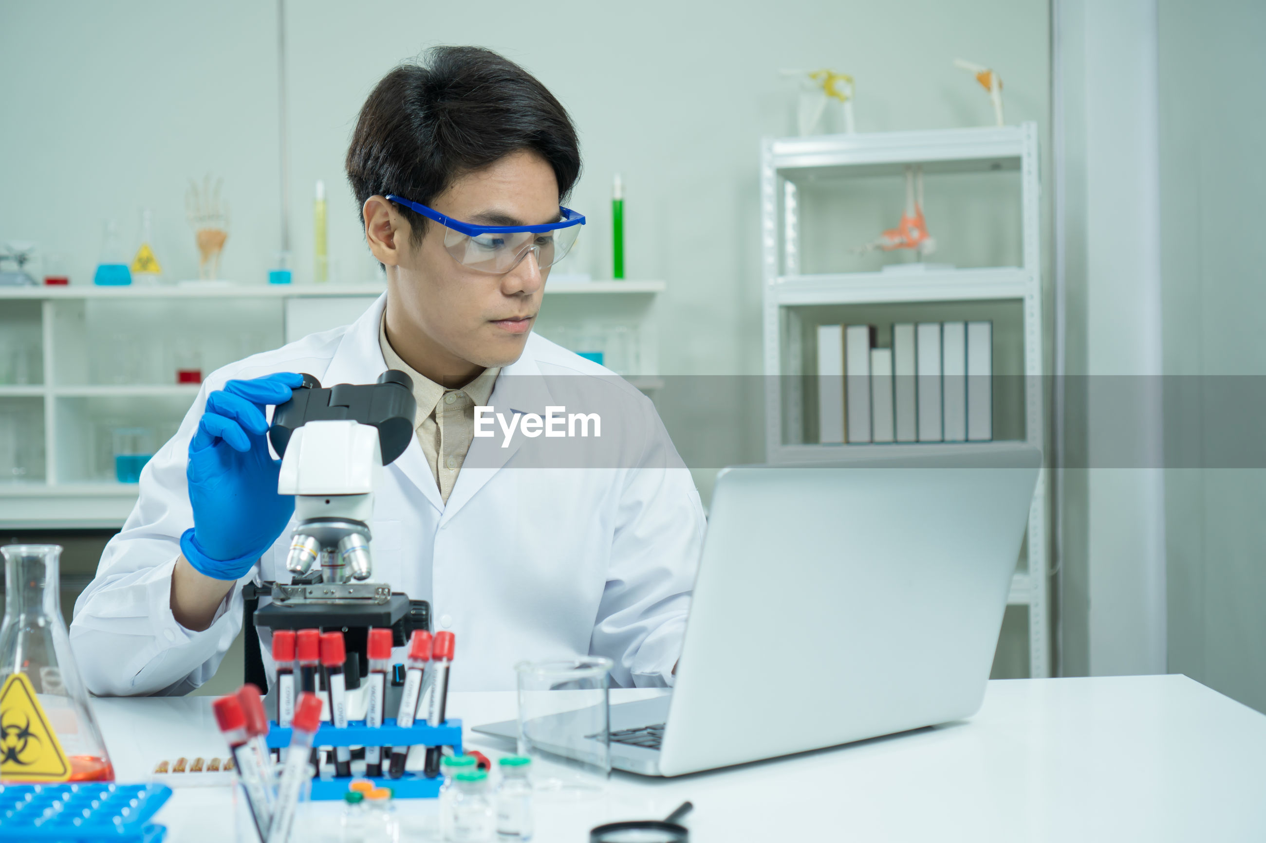 Scientist using microscope and laptop at laboratory