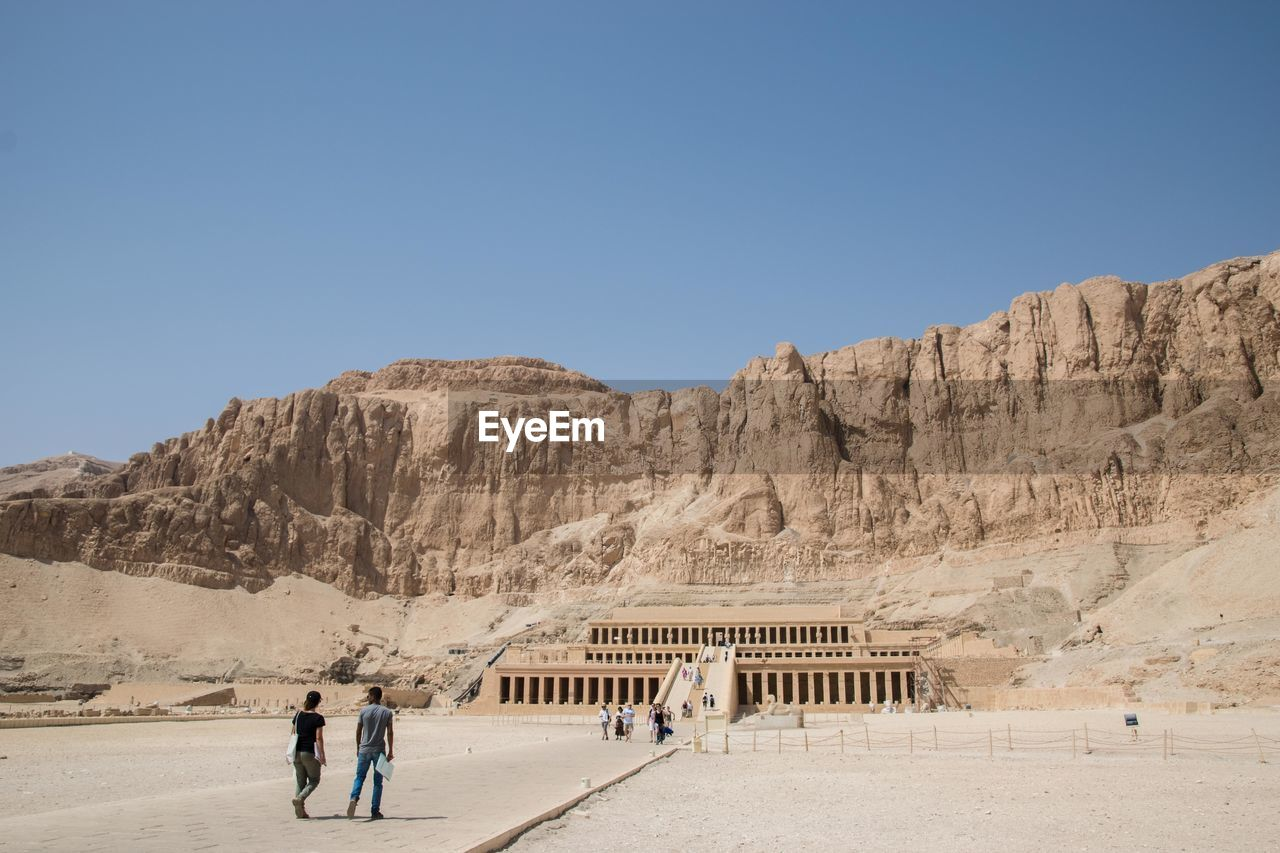 Rear View Of People Walking At Desert Against Clear Sky During Sunny Day