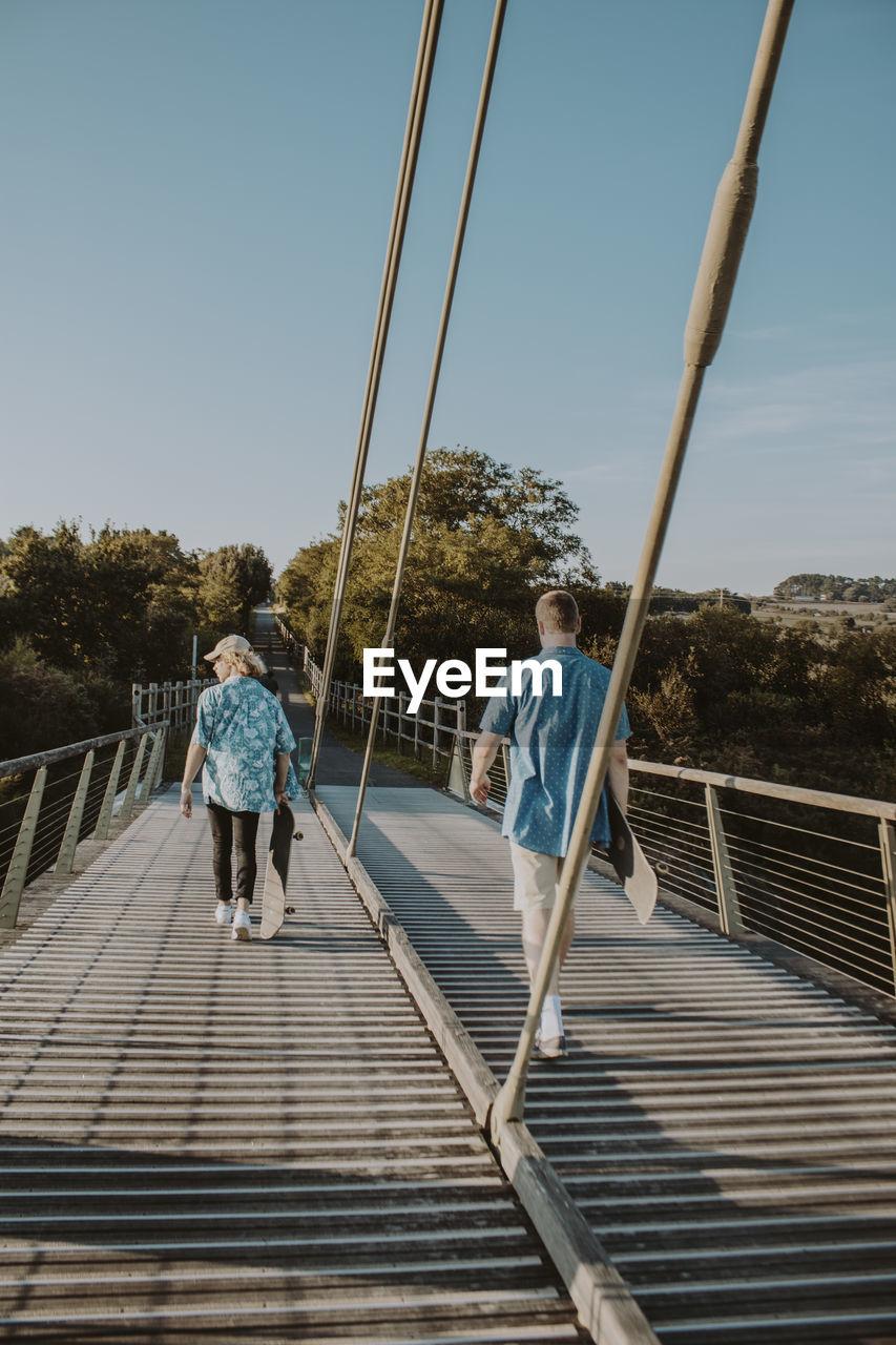 Rear view of people walking on footbridge against sky