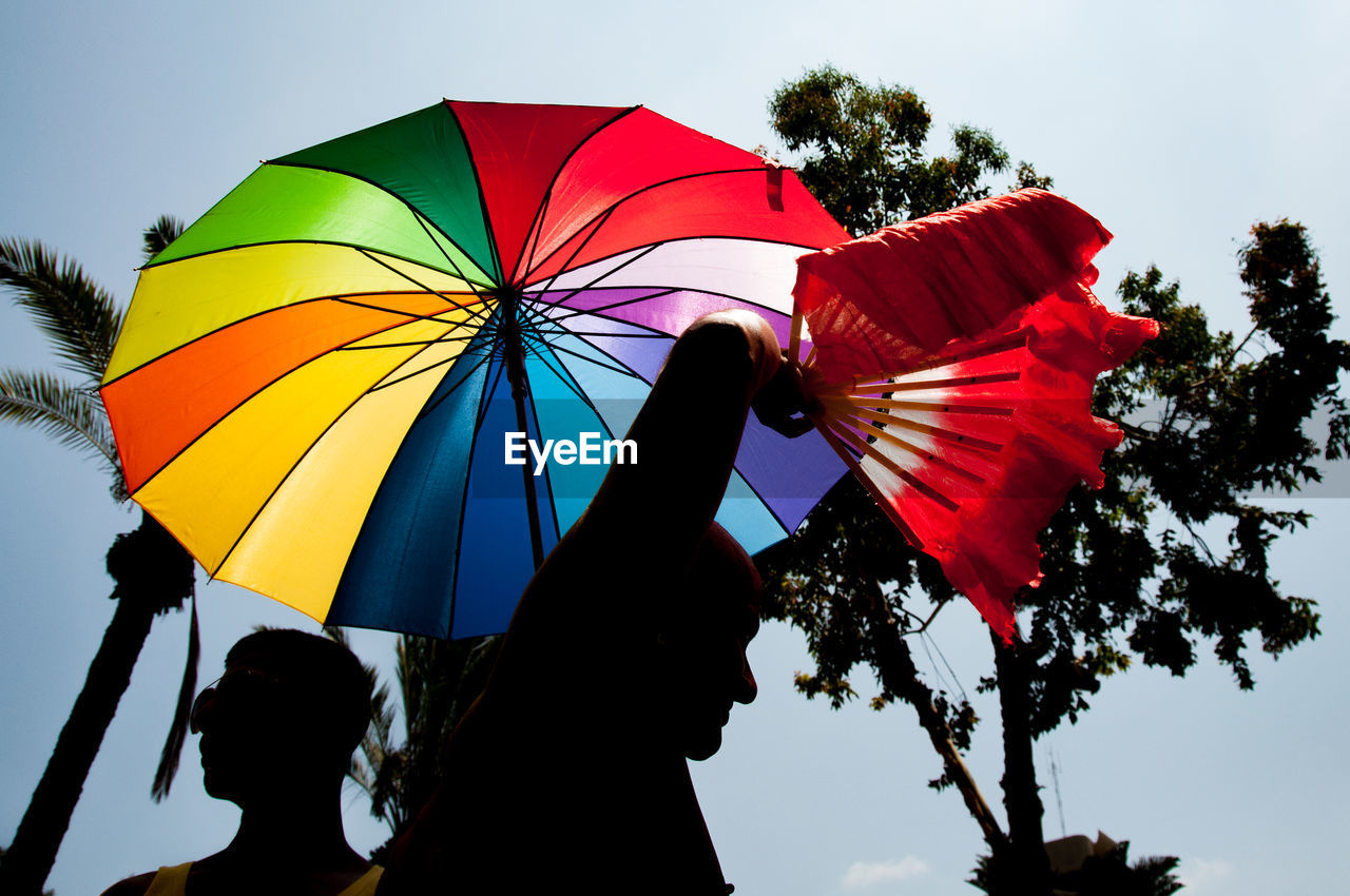 Low angle view of men and colorful umbrella against sky