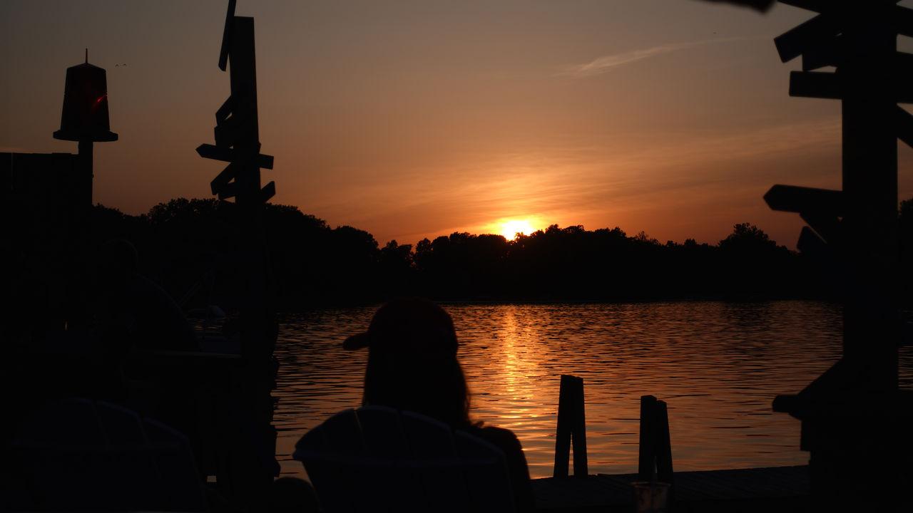 SILHOUETTE PEOPLE SITTING ON LAKE AT SUNSET