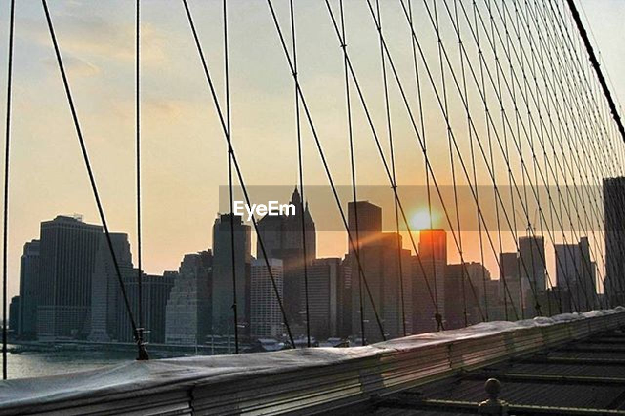 skyscraper, sunset, architecture, city, downtown district, modern, urban skyline, built structure, cityscape, business finance and industry, dusk, office building exterior, outdoors, sky, building exterior, no people, city life, sunlight, suspension bridge, bridge - man made structure, travel destinations, business, futuristic, illuminated, day