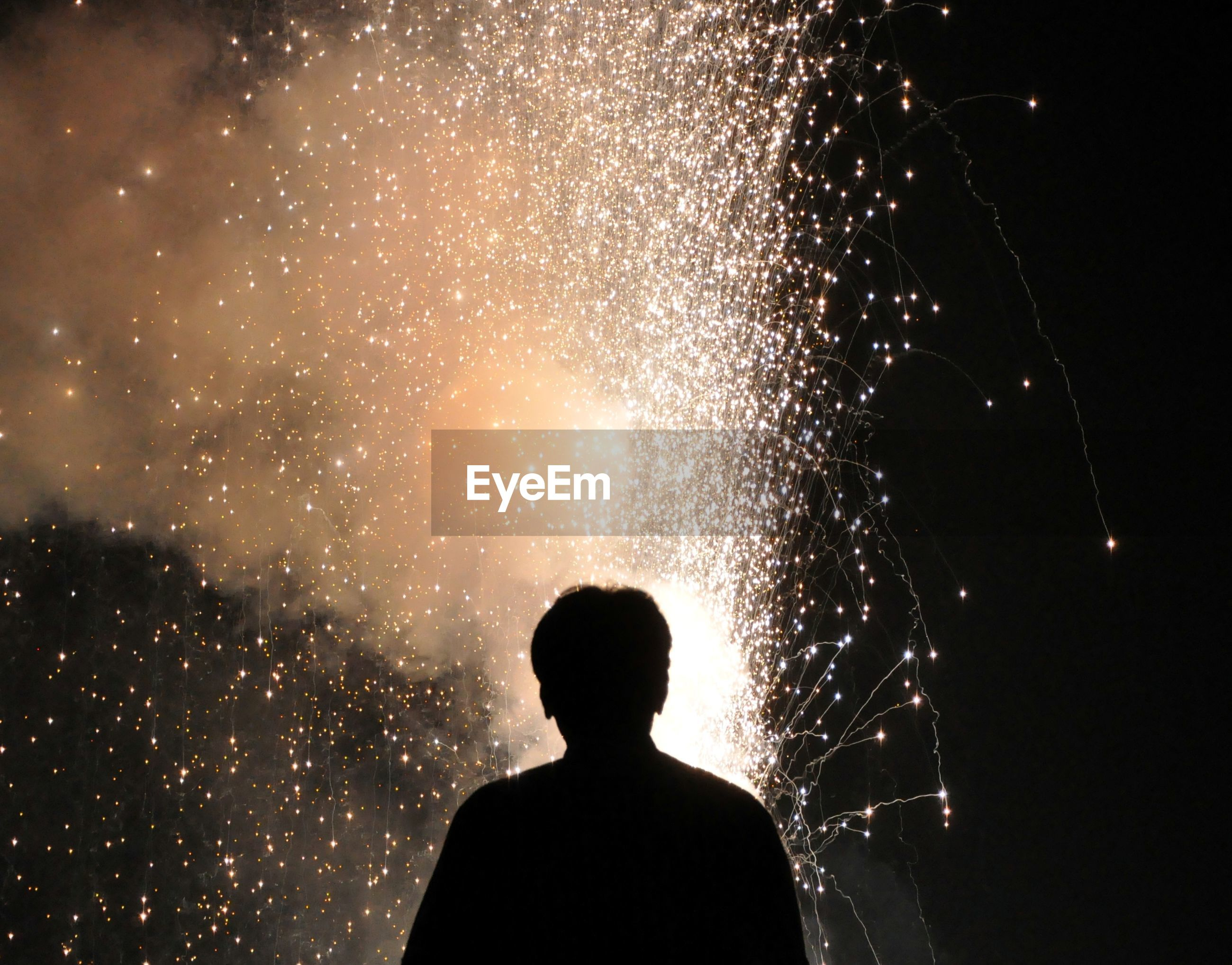 Rear view of silhouette man looking at firework against sky