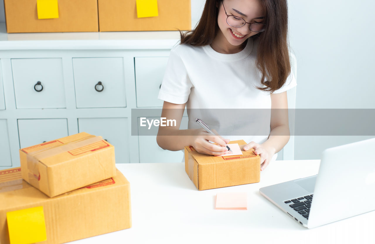 Smiling woman writing on cardboard box at office