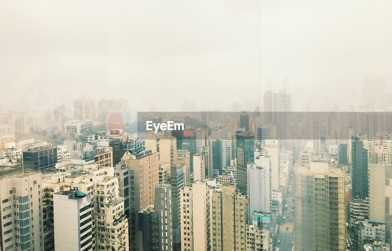 city, building exterior, building, built structure, architecture, skyscraper, sky, cityscape, office building exterior, residential district, no people, landscape, high angle view, fog, nature, modern, city life, tall - high, outdoors, apartment, air pollution, smog, pollution, financial district