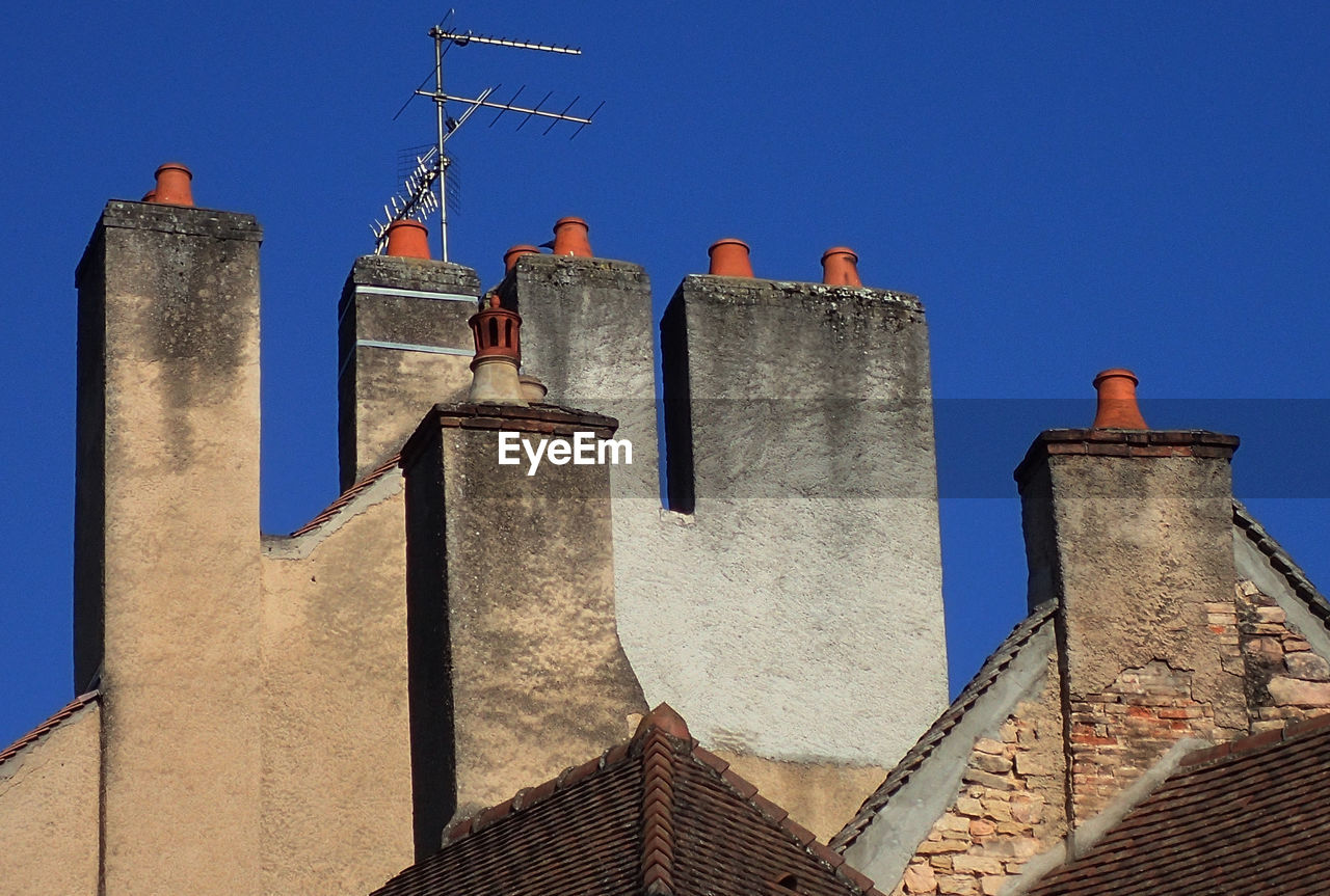 Low Angle View Of Old Building With Chimneys Against Sky