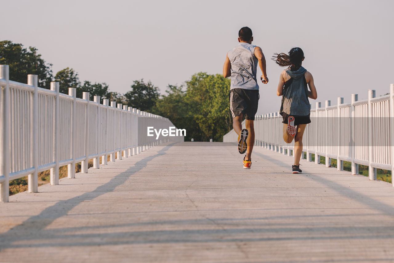 full length, rear view, real people, lifestyles, casual clothing, the way forward, direction, leisure activity, footpath, men, railing, sky, nature, day, walking, people, women, connection, two people, bridge, diminishing perspective, footbridge, outdoors, shorts