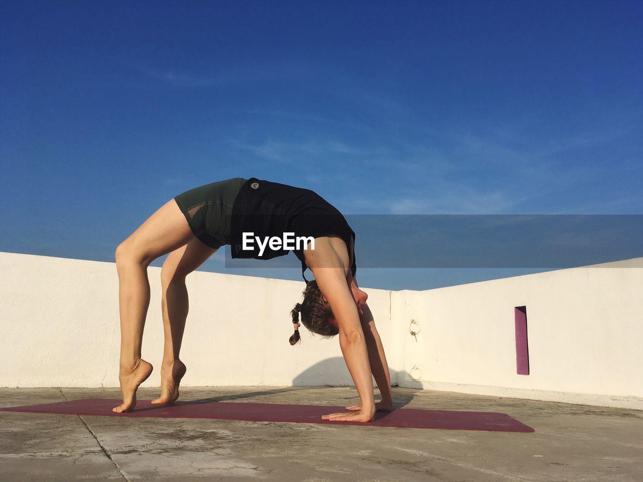 Woman bending over backwards against blue sky