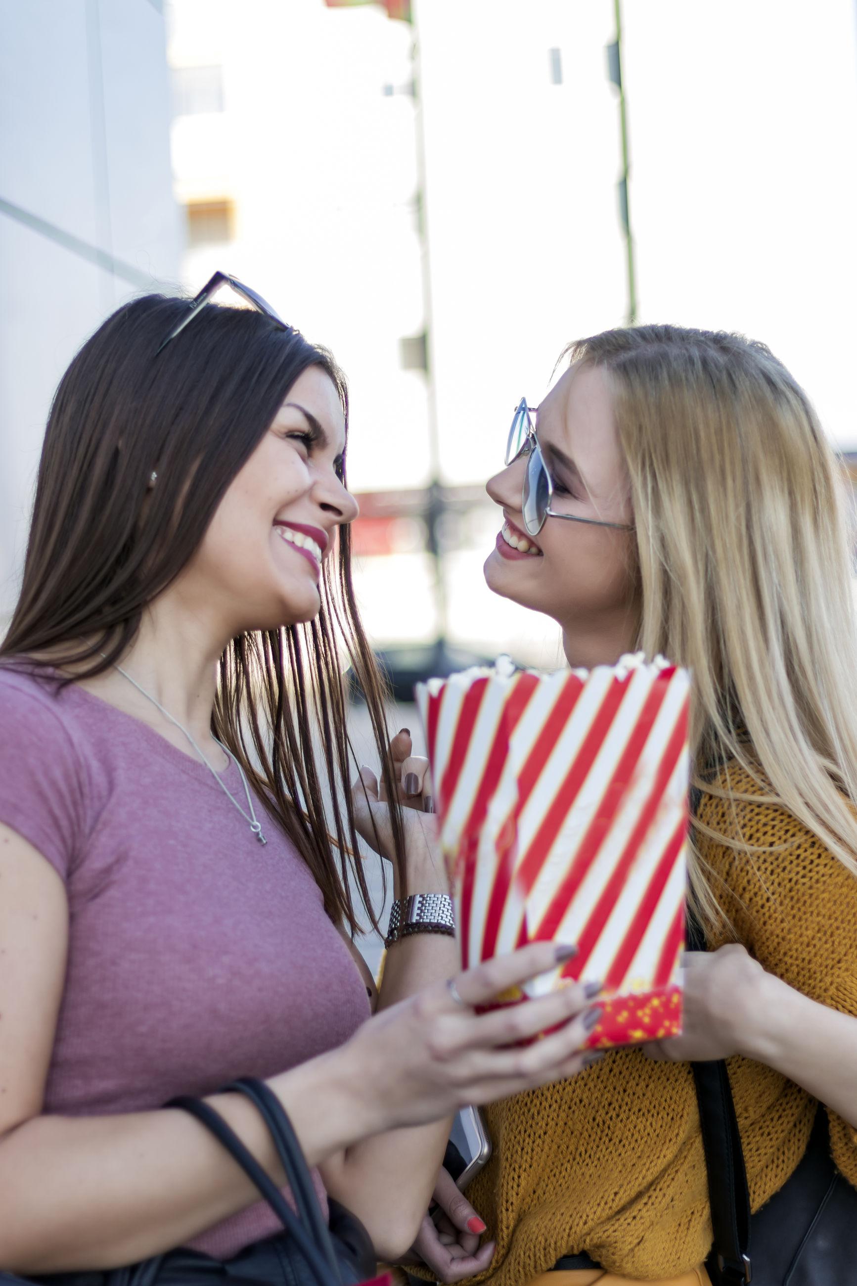 Smiling friends having popcorn in city
