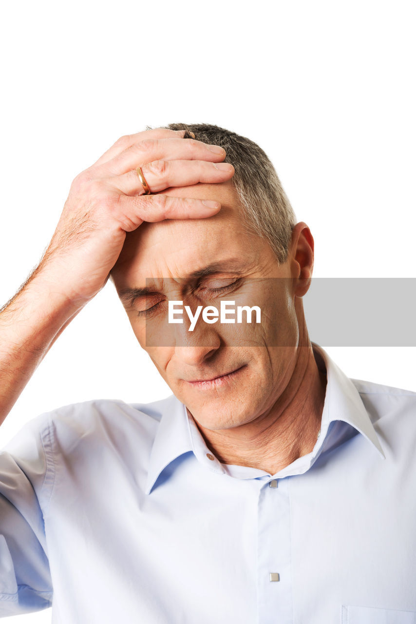 Businessman with headache standing against gray background