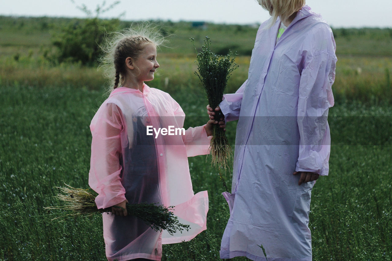 Daughter And Mother Standing On Field
