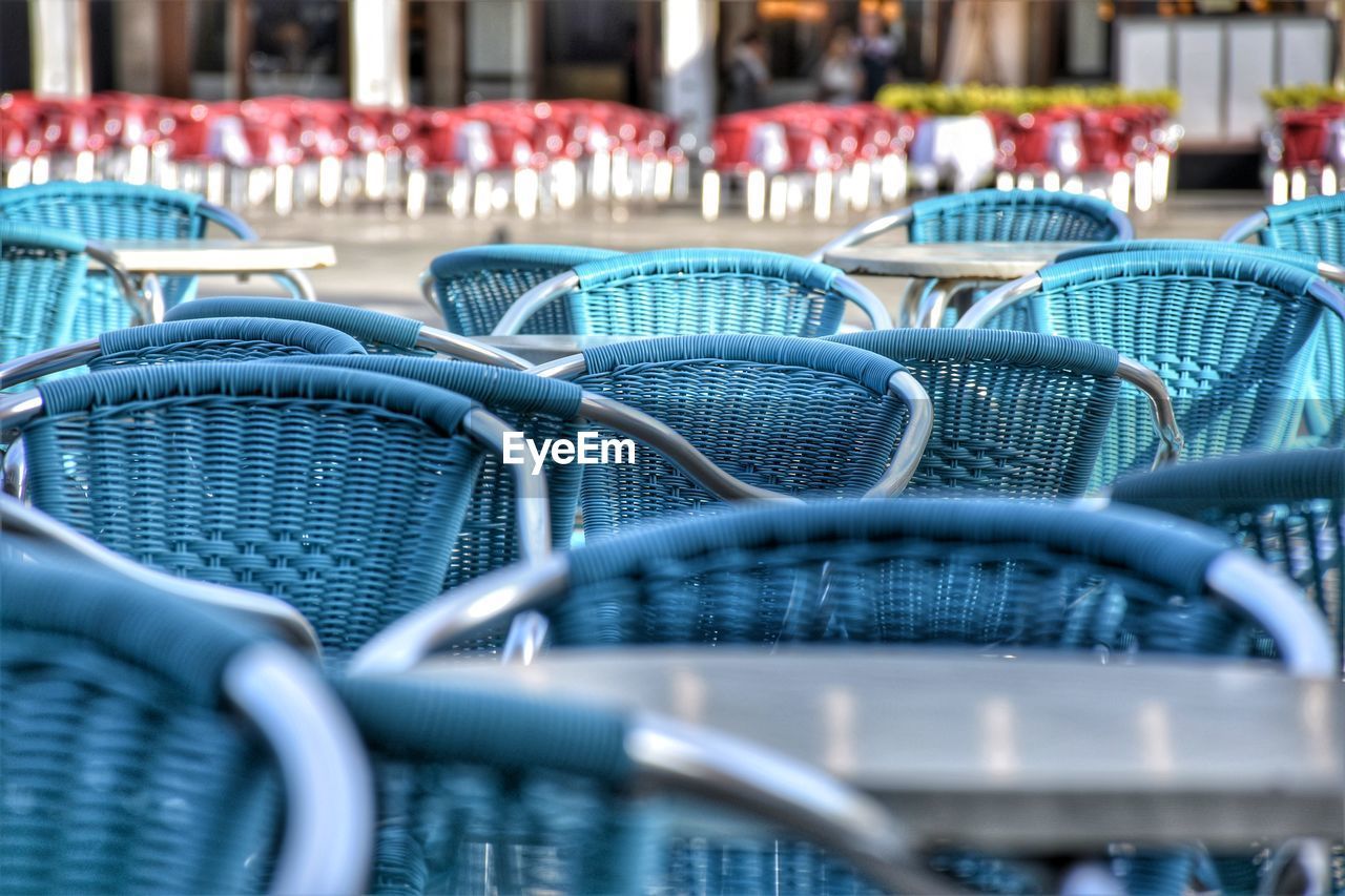 chair, seat, empty, in a row, no people, selective focus, metal, absence, day, blue, close-up, shopping cart, arrangement, repetition, still life, large group of objects, outdoors, table, business, group of objects, consumerism, setting