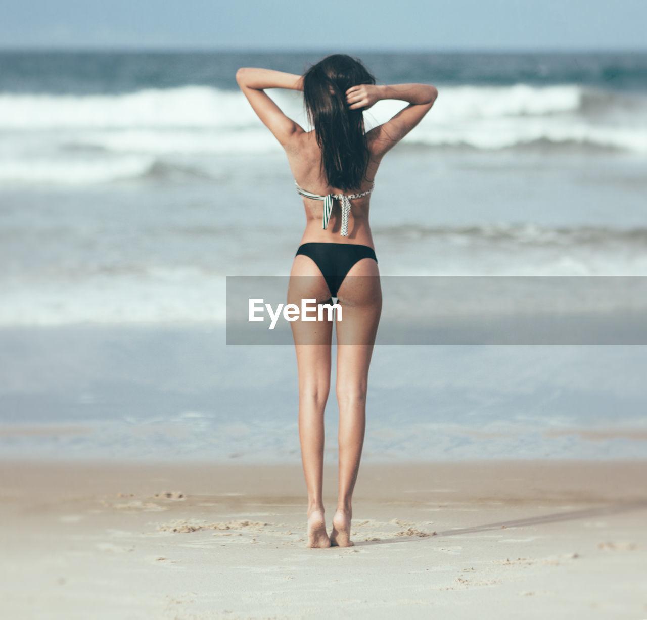Full Length Rear View Of Beautiful Woman Standing At Beach