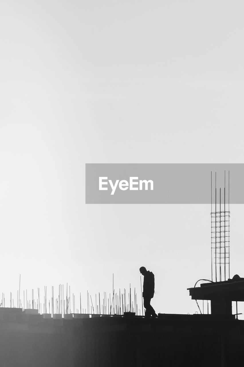 Silhouette man at construction site against clear sky