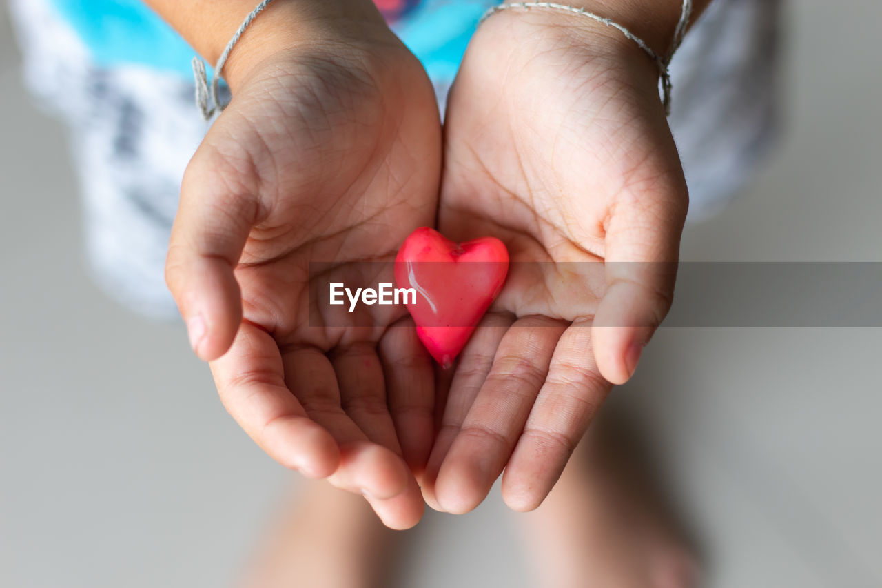 heart shape, love, positive emotion, human hand, hand, emotion, red, one person, real people, holding, human body part, close-up, focus on foreground, lifestyles, unrecognizable person, finger, creativity, human finger, indoors, hands cupped, valentine's day - holiday