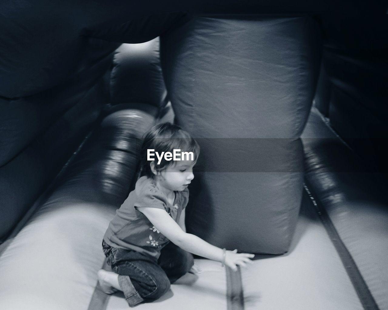 Side view of girl plying in bouncy castle