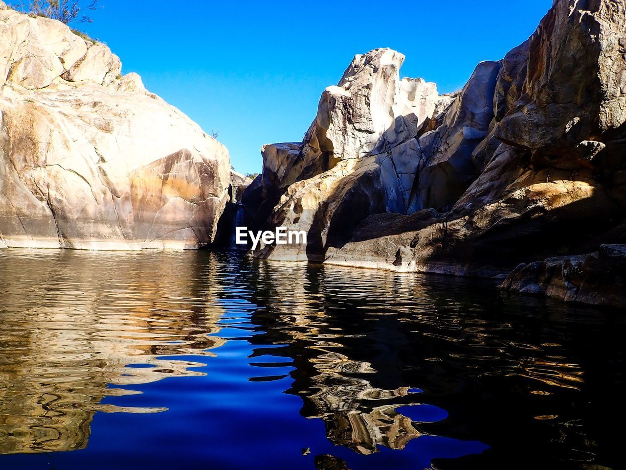 water, rock, reflection, sky, beauty in nature, rock - object, scenics - nature, rock formation, nature, solid, waterfront, tranquil scene, blue, tranquility, no people, non-urban scene, day, lake, clear sky, outdoors, eroded, formation