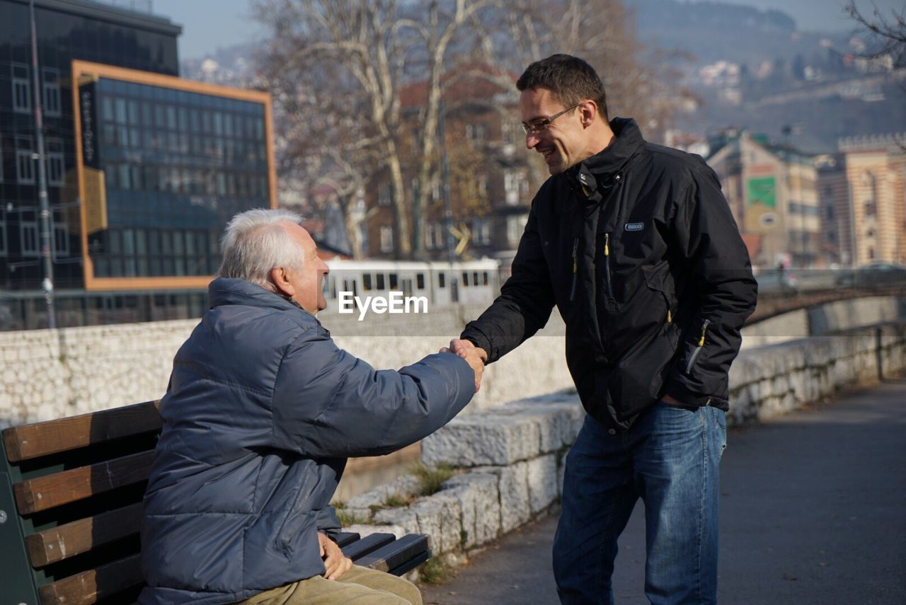 two people, senior adult, outdoors, men, day, togetherness, city, real people, greeting, architecture, building exterior, human hand, young adult, adult, adults only, people
