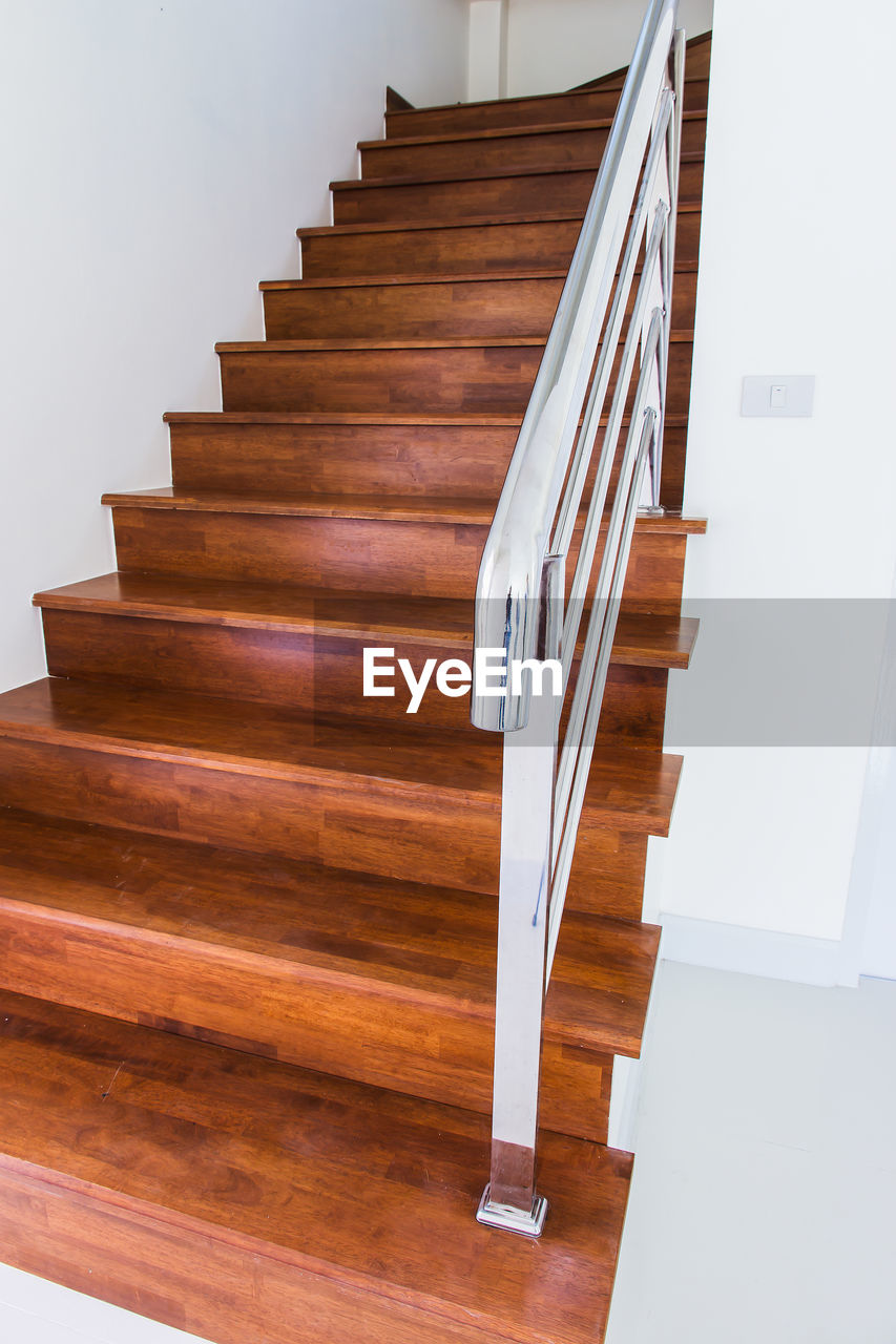 staircase, architecture, railing, indoors, built structure, steps and staircases, wood - material, no people, building, in a row, spiral, wood, moving up, home interior, absence, brown, house, flooring, empty, low angle view, luxury