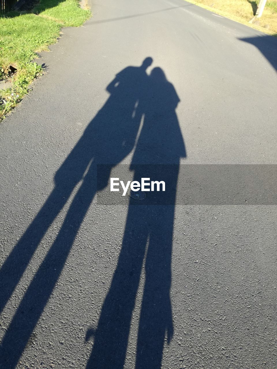 shadow, focus on shadow, sunlight, long shadow - shadow, two people, real people, high angle view, men, togetherness, day, lifestyles, road, outdoors, people