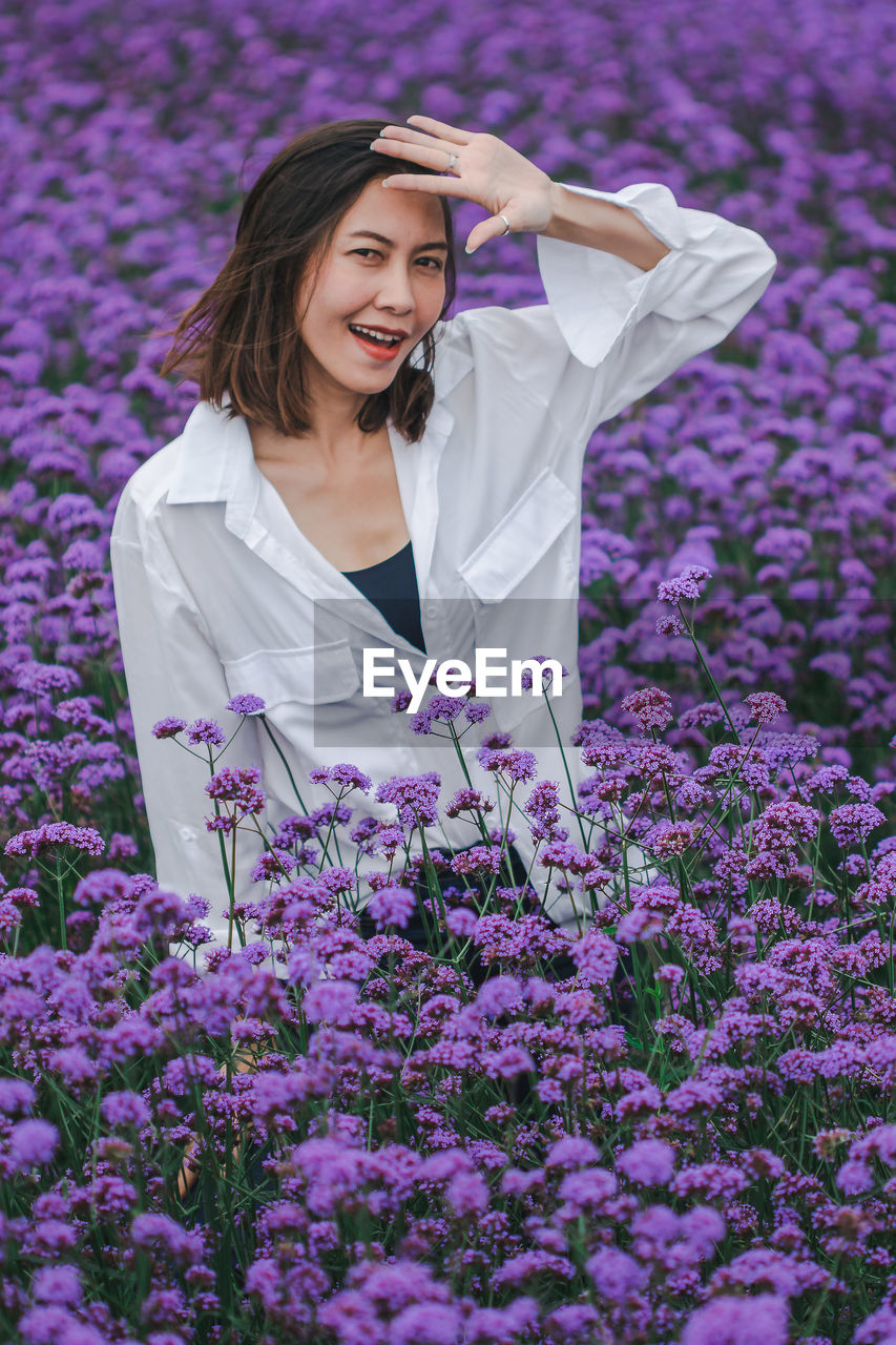 flowering plant, flower, one person, young adult, young women, women, real people, smiling, plant, lifestyles, leisure activity, beauty in nature, freshness, front view, purple, three quarter length, standing, happiness, adult, beautiful woman, hairstyle, outdoors