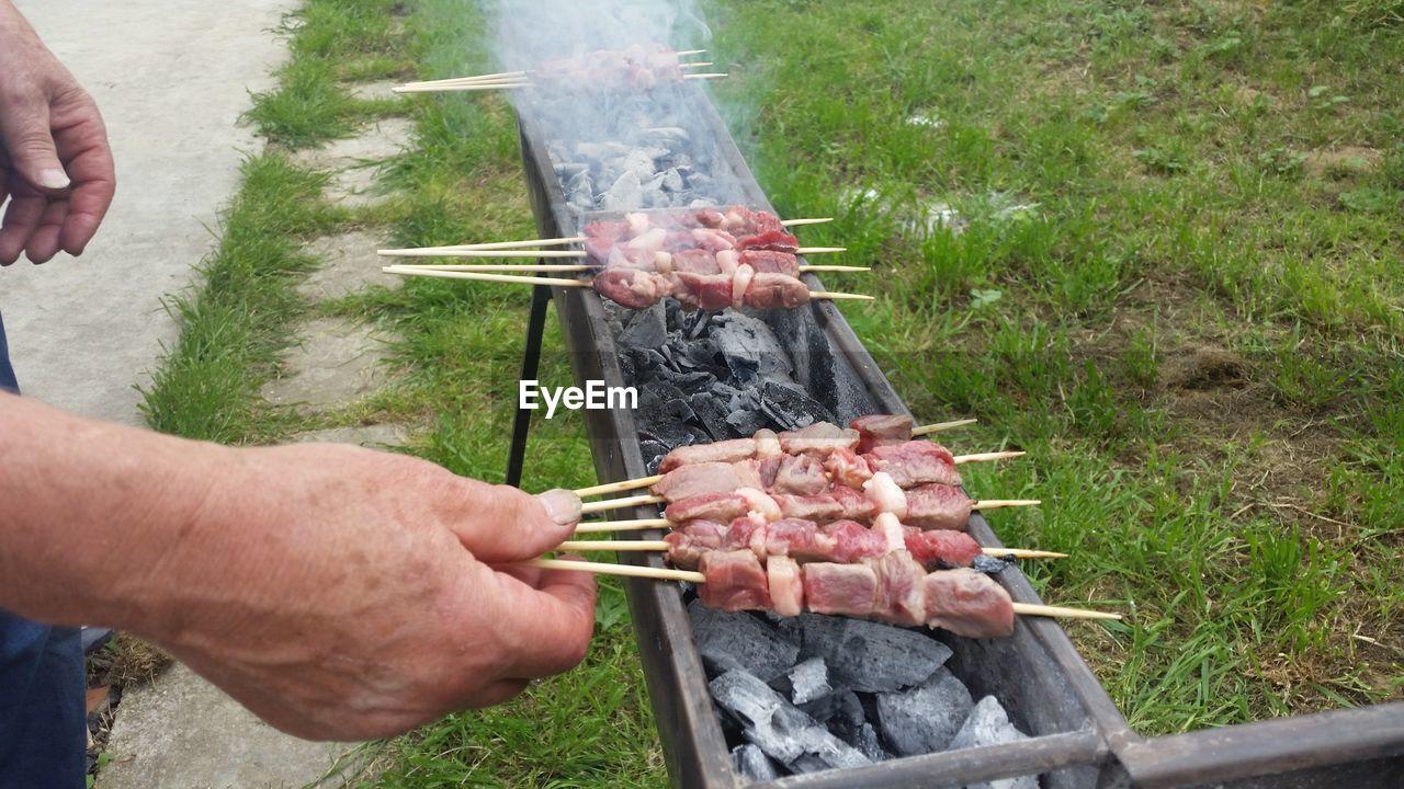 Cropped image of man preparing roasting meat skewers at yard