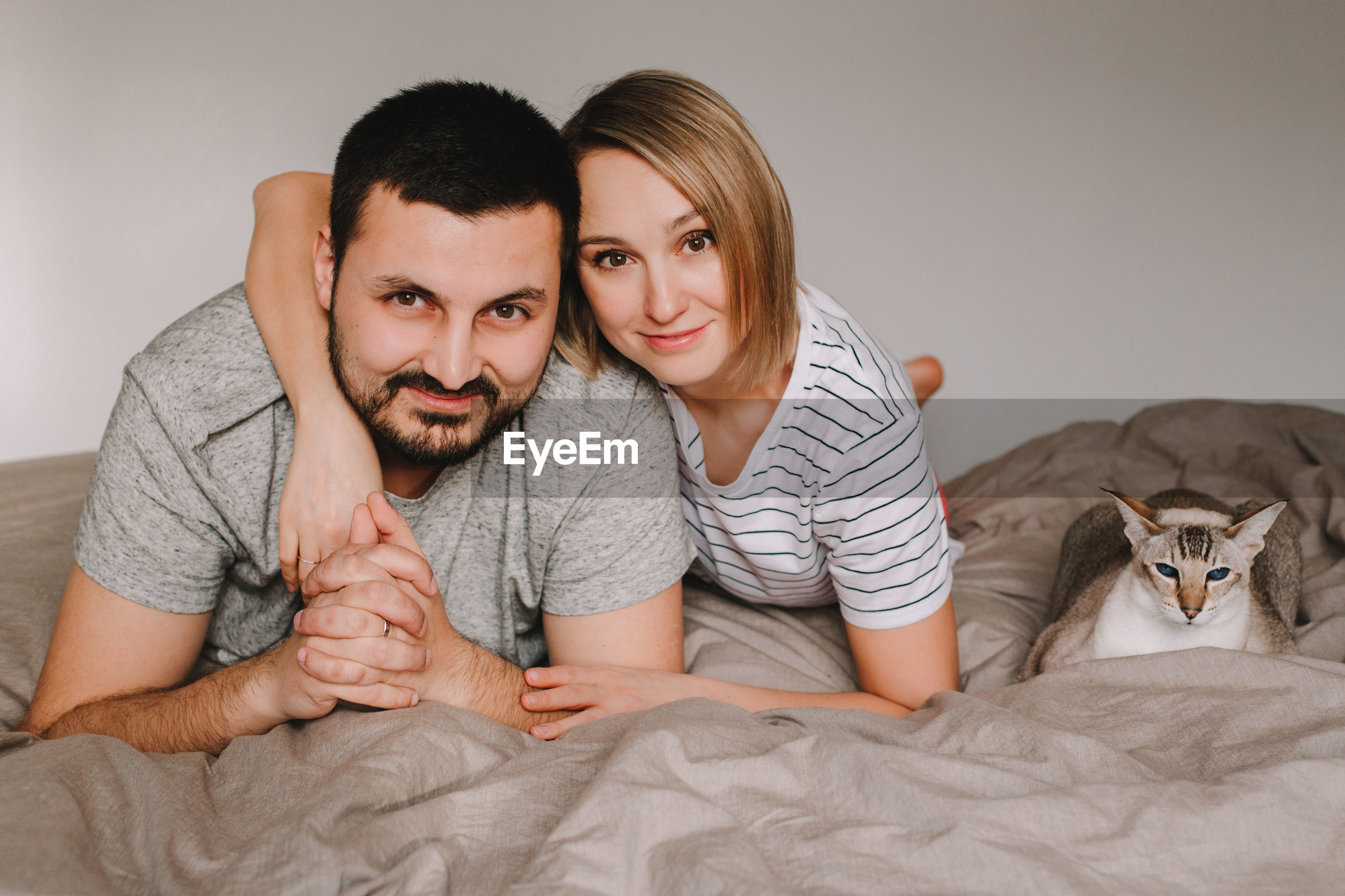 Portrait of smiling couple lying by cat on bed at home