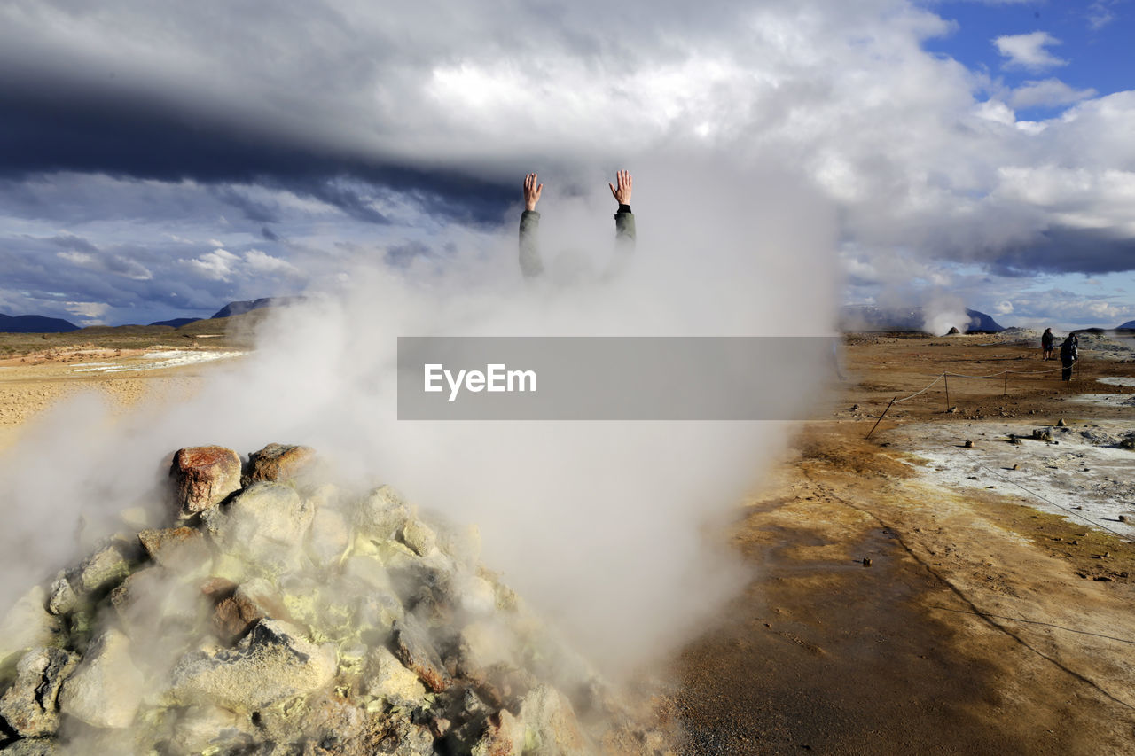 Cropped Hand Of Person At Volcanic Landscape