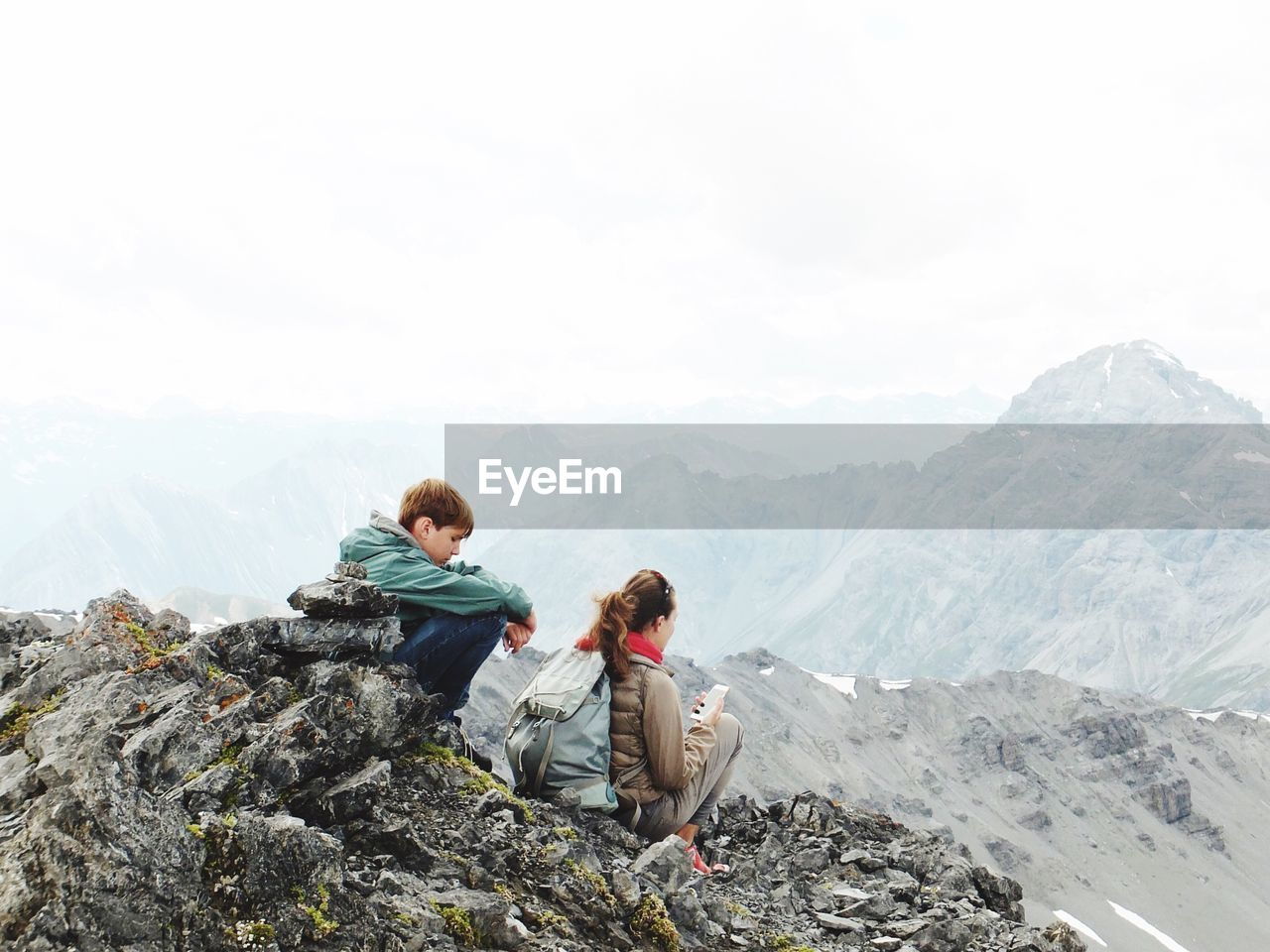 Friends sitting on cliff against sky during foggy weather