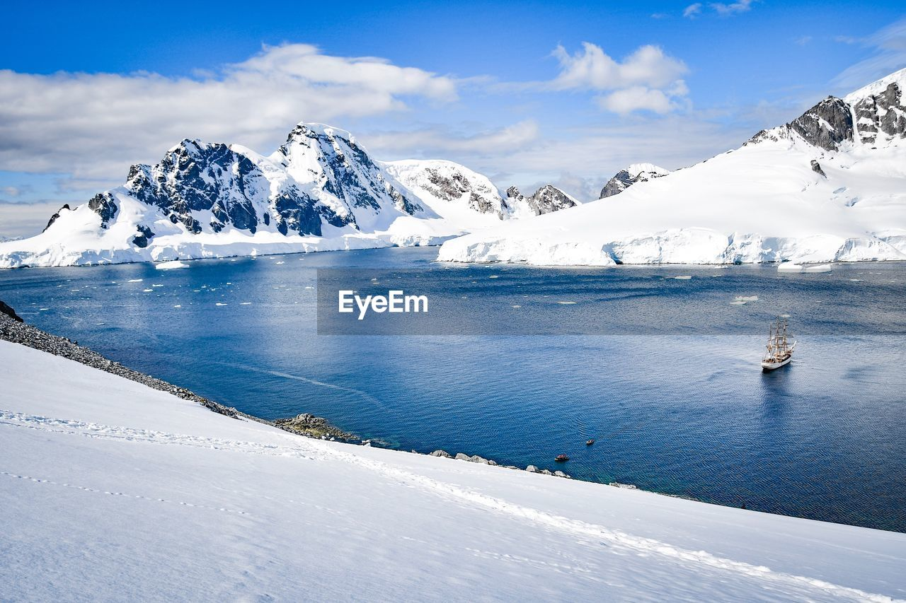 cold temperature, winter, snow, beauty in nature, scenics - nature, mountain, water, sky, snowcapped mountain, nature, non-urban scene, tranquil scene, day, tranquility, white color, cloud - sky, mountain range, environment, ice, mountain peak