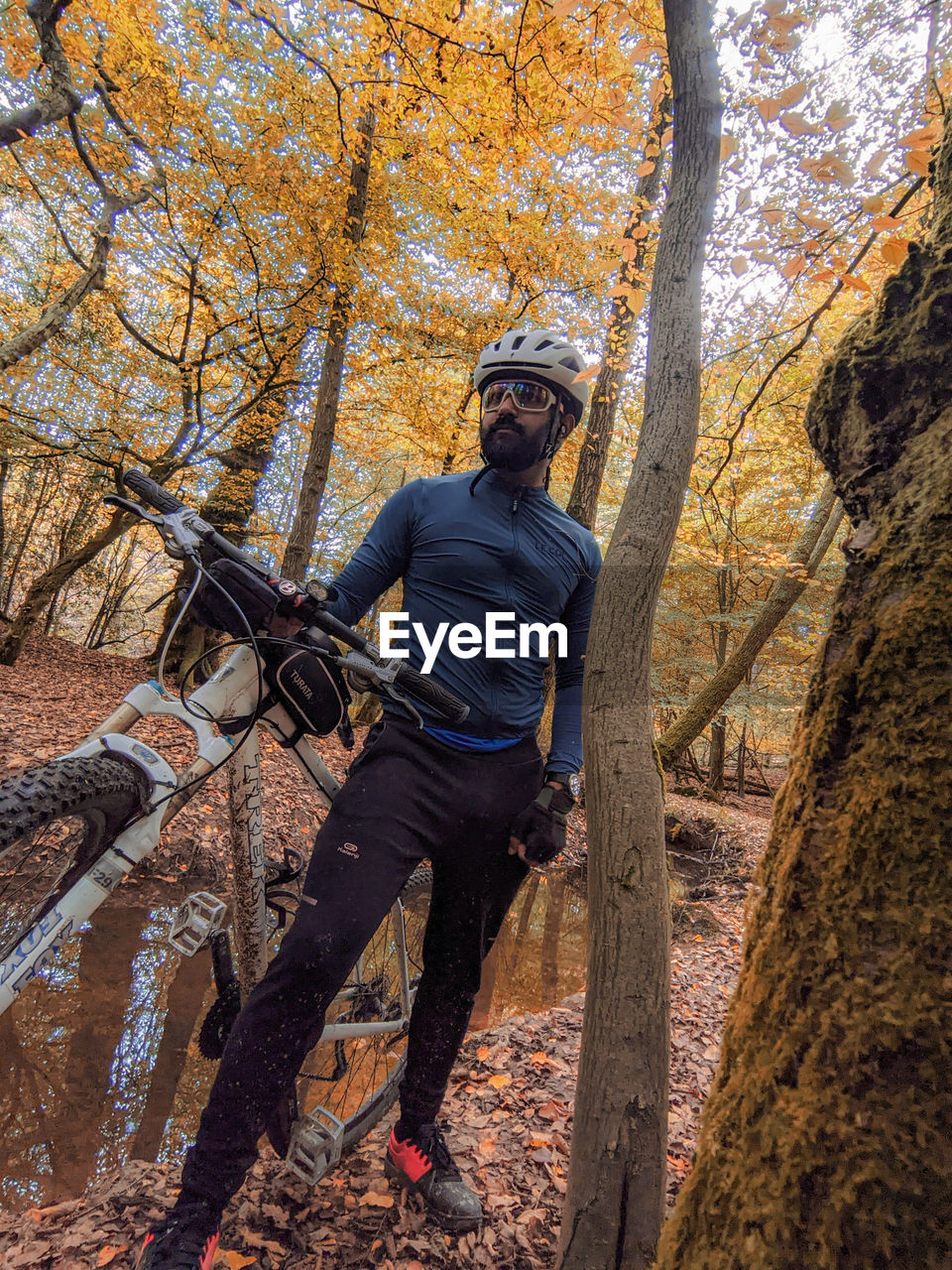 MAN STANDING BY TREE TRUNK IN FOREST