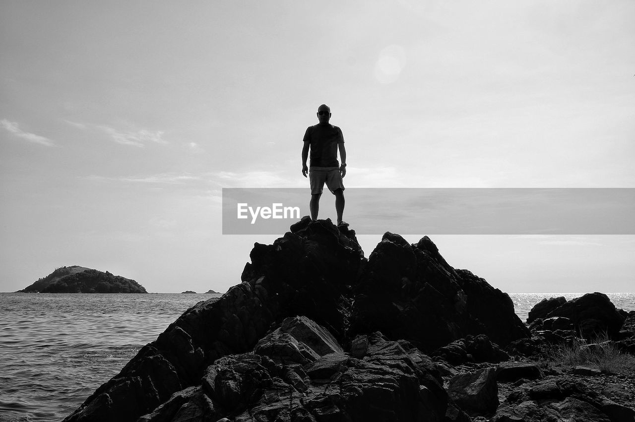 Rear view of man standing on rock at sea shore against sky