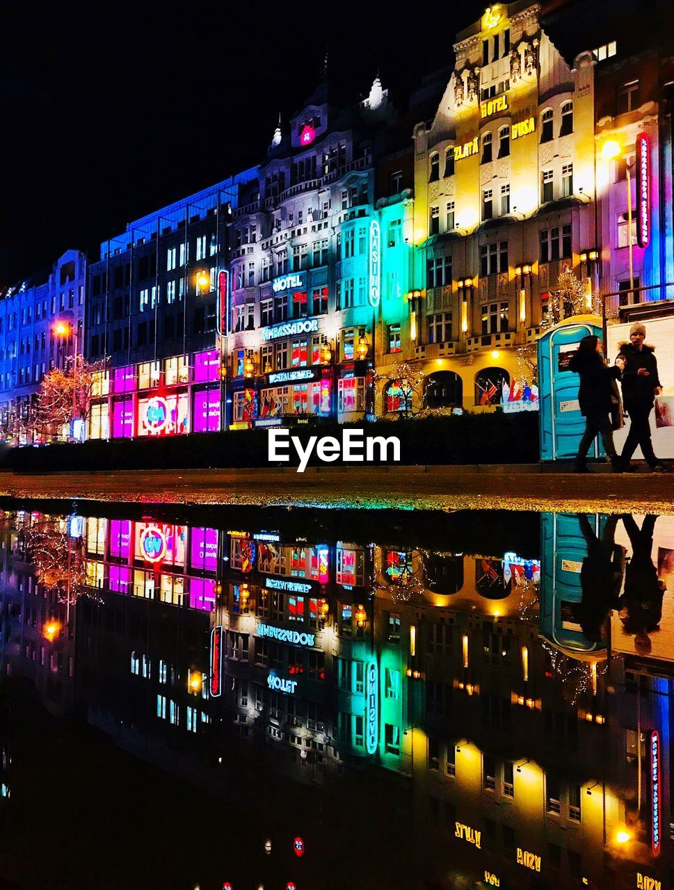ILLUMINATED BUILDINGS BY LAKE AGAINST SKY IN CITY